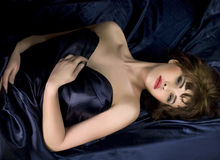 Woman lying on dark blue silk Royalty Free Stock Photos