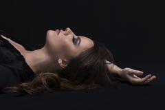 Woman lying in the dark Stock Photo