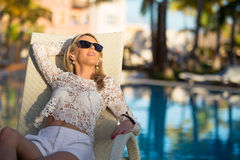 Woman lying in deck chair by the pool Royalty Free Stock Images
