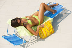Woman lying on deckchair by swimming-pool. Beautiful young woman lying on deckchair by swimming-pool Stock Image