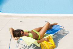 Woman lying on deckchair by swimming-pool Royalty Free Stock Photo
