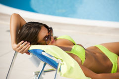 Woman lying on deckchair by swimming-pool. Beautiful young woman lying on deckchair by swimming-pool, close-up Stock Images