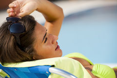 Woman lying on deckchair by swimming-pool Royalty Free Stock Image