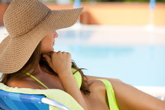 Woman lying on deckchair by swimming-pool Royalty Free Stock Photos