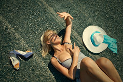 Woman lying on a desert road Stock Photography