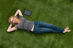 Woman Lying With Digital Tablet On Green Grass Royalty Free Stock Images