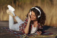 Woman lying on the docks listening to the music stock photography