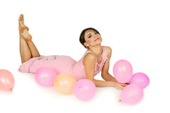 Woman lying down with air balloons Stock Photography