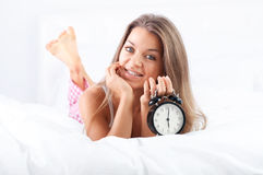 Woman lying down on bed ang holding alarm clock. Bedtime collection: woman lying down on bed ang holding alarm clock Stock Image