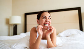 Woman lying down in bed and smiling. Royalty Free Stock Images