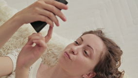 Woman lying down on the bed using her cellphone. stock video footage