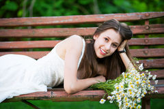 Woman lying down on bench Stock Photo