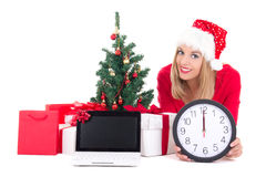 Woman lying down with clock,notebook,  christmas tree and gifts Royalty Free Stock Photography