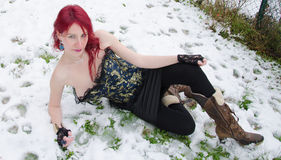 Woman lying down on a frozen snow Stock Image