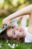 Woman lying down on grass with book Stock Image