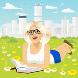 Woman lying down on grass reading book. Attractive blonde woman with glasses lying down on grass reading book in a city peaceful park Royalty Free Stock Photos