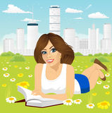 Woman lying down on grass reading book. Attractive brunette woman with glasses lying down on grass reading book in a city peaceful park Royalty Free Stock Photo