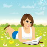 Woman lying down on grass reading book Royalty Free Stock Photography