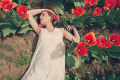 Woman lying down on ground in tulips Royalty Free Stock Images