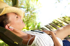 Woman lying down on hammock listening to music Royalty Free Stock Images