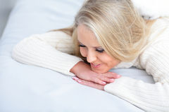 Woman lying down on her bed Stock Images