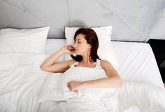 Woman lying down on her bed at home. Stock Photo