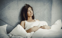 Woman lying down on her bed at home. Stock Images