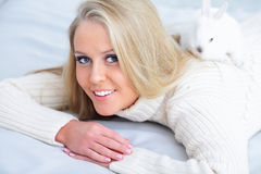 Woman lying down on her bed with rabbit Royalty Free Stock Photo