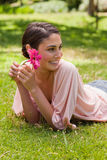 Woman lying down while looking to her side and holding a flower Stock Images