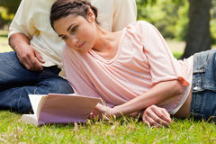 Woman lying down next to her friend. While reading a book Royalty Free Stock Photos