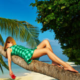 Woman lying down on a palm tree at tropical beach. Woman in green dress lying down on a palm tree at tropical beach, Maldives Stock Images
