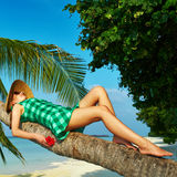Woman lying down on a palm tree at tropical beach. Woman in green dress lying down on a palm tree at tropical beach, Maldives Stock Photography