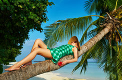 Woman lying down on a palm tree at tropical beach. Woman in green dress lying down on a palm tree at tropical beach, Maldives Stock Photo