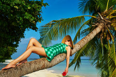 Woman lying down on a palm tree at tropical beach. Woman in green dress lying down on a palm tree at tropical beach, Maldives Royalty Free Stock Image