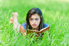 Woman lying down reading book Royalty Free Stock Images