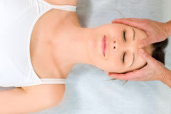 Woman lying down receiving head massage Stock Photo