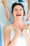 woman lying down smiling and receiving head massa Royalty Free Stock Image