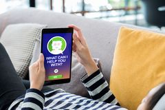 Woman lying down on sofa using tablet ask question chat bot at home.digital technology lifestyle royalty free stock photography