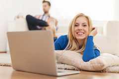 Woman lying down and working on laptop Stock Photo