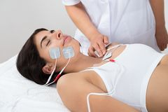 Woman lying with electrodes on chest and face Royalty Free Stock Photo