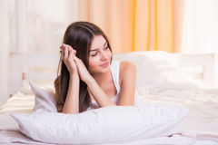 A woman lying at the end of the bed underneath the quilt and smiling, with her head resting upon her hand Stock Image