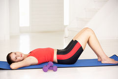 Woman lying on exercise mat Royalty Free Stock Photos