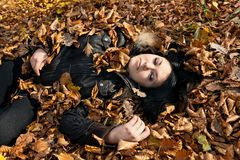 Woman lying in fallen leaves Royalty Free Stock Photos