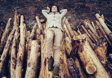 Woman lying on felled tree trunk Stock Images