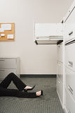 Woman lying by filing cabinet stock image