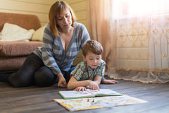 Woman lying on the floor engaged in lessons with a young son. Stock Photos
