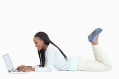 Woman lying on the floor with her laptop Stock Photo
