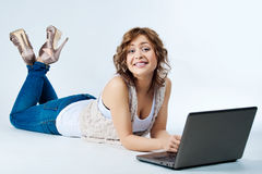 Woman lying on floor with laptop Royalty Free Stock Photography