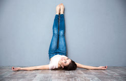 Woman lying on the floor with legs raised up Royalty Free Stock Photos
