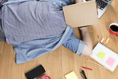 Woman lying on floor with mobile phone, notebook and laptop Royalty Free Stock Images